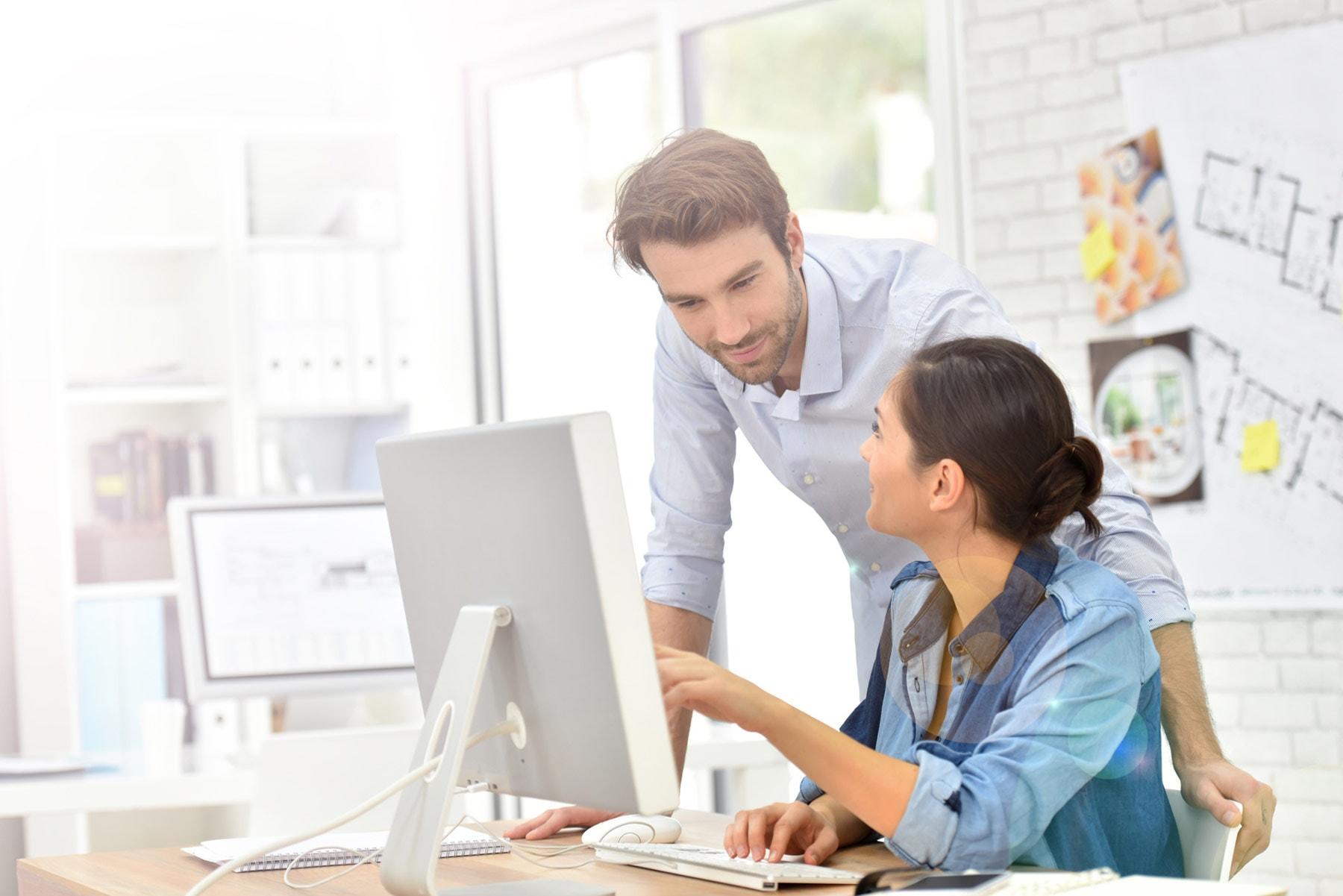 Mann und Frau vor Bildschirm im Büro