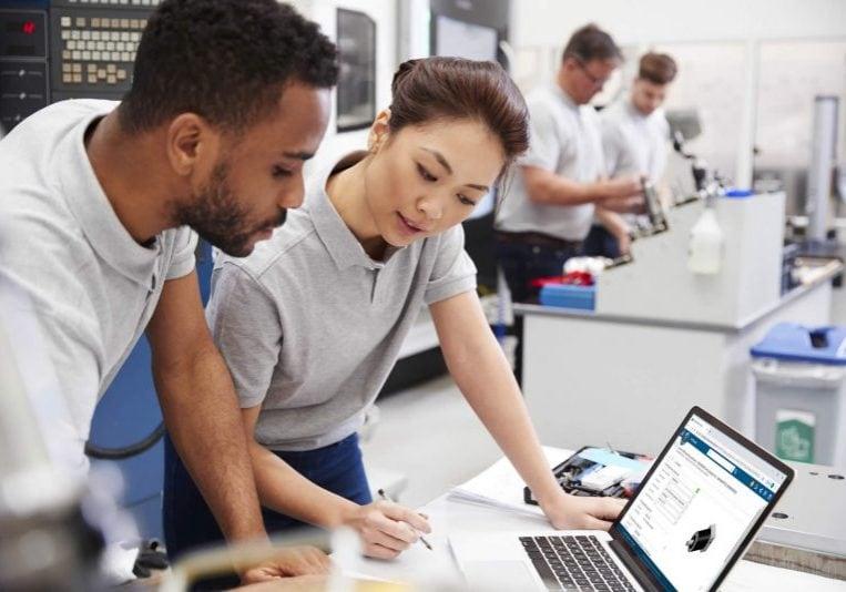 Mann und Frau unterhalten sich vor Laptop mit 3DEXPERIENCE Anwendung