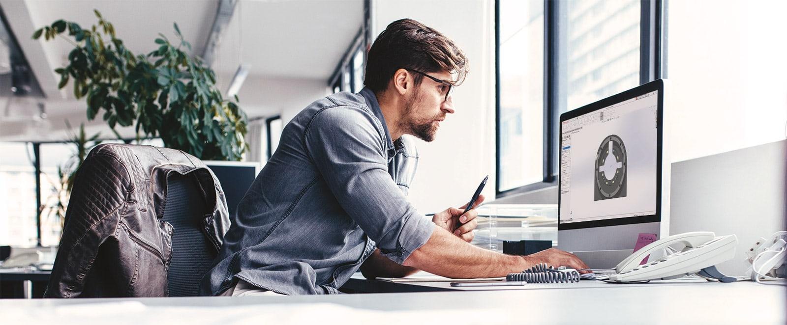 Konstrukteur am Schreibtisch mit Bildschirm