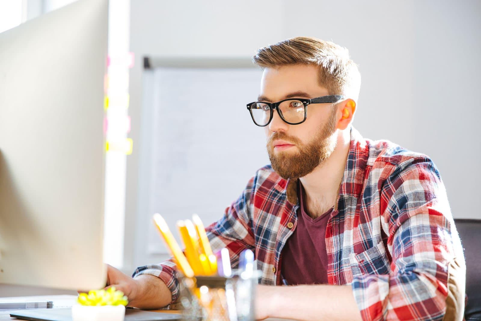 Mann mit Brille vor Bildschirm