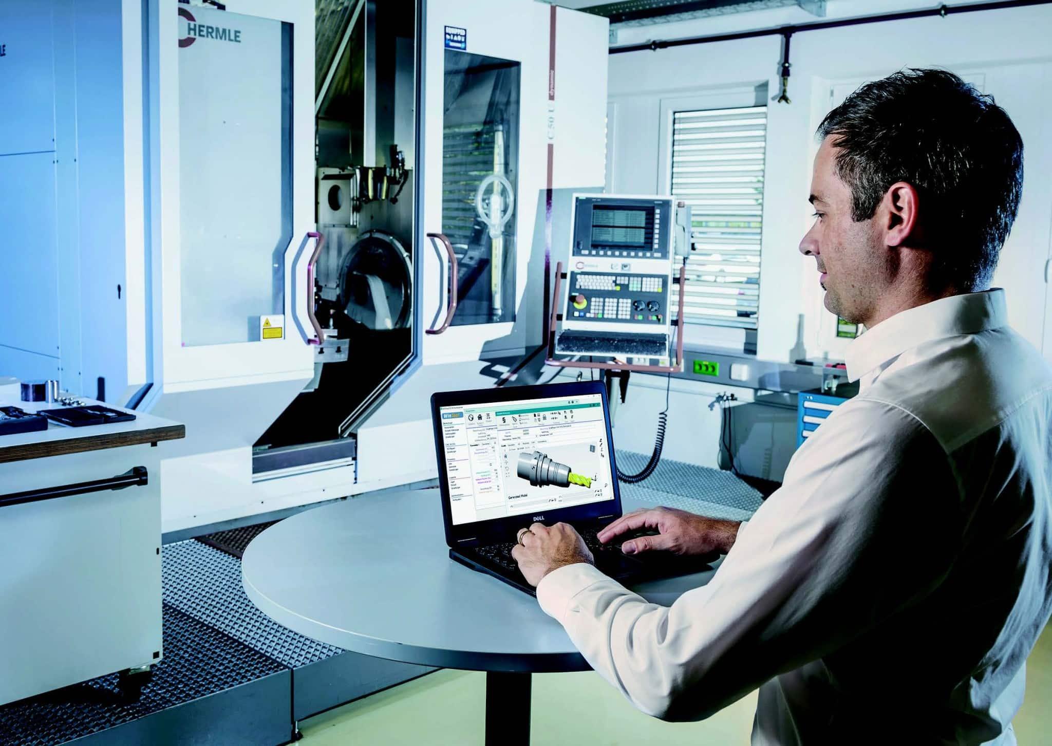 Mann vor Maschine mit Laptop und der Werkzeugverwaltunssoftware WINTool