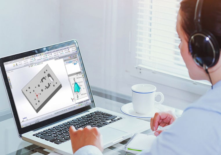 Frau mit Headset vor Laptop mit SOLIDWORKS Desktop